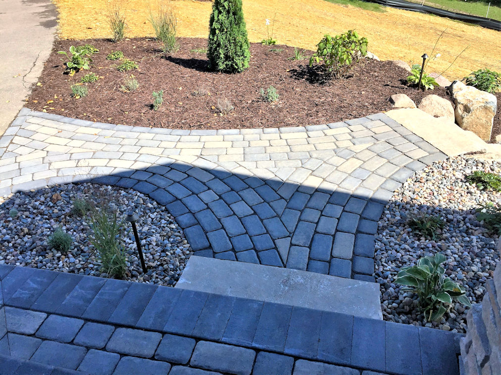 This sidewalk uses pavers to create an intricately patterned walkway.