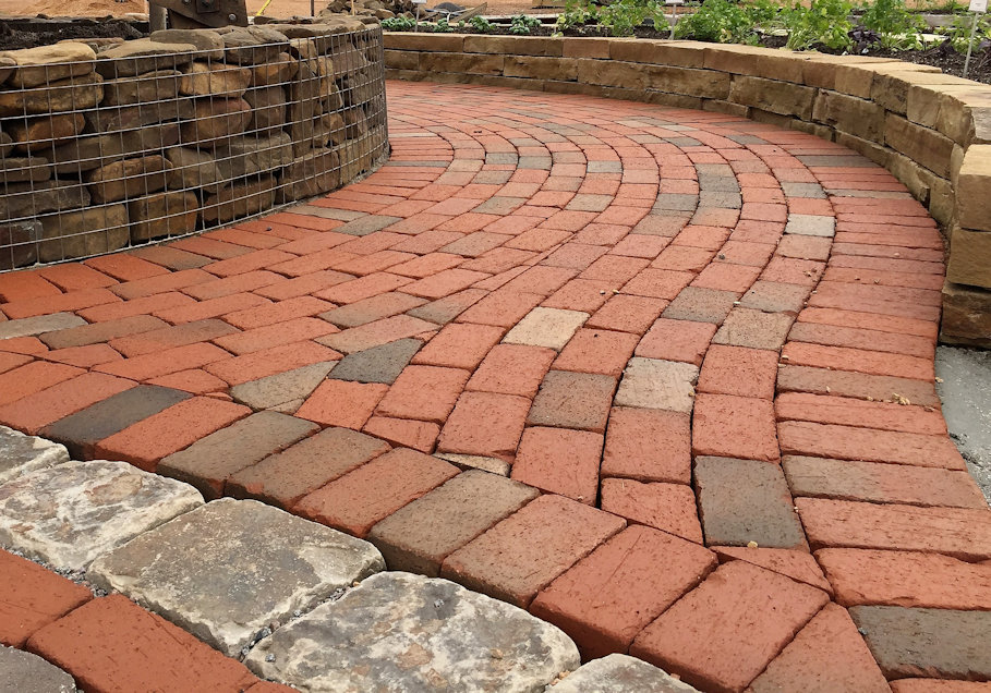 This curved brick path has decorative stone blocks adding dimension to the path.